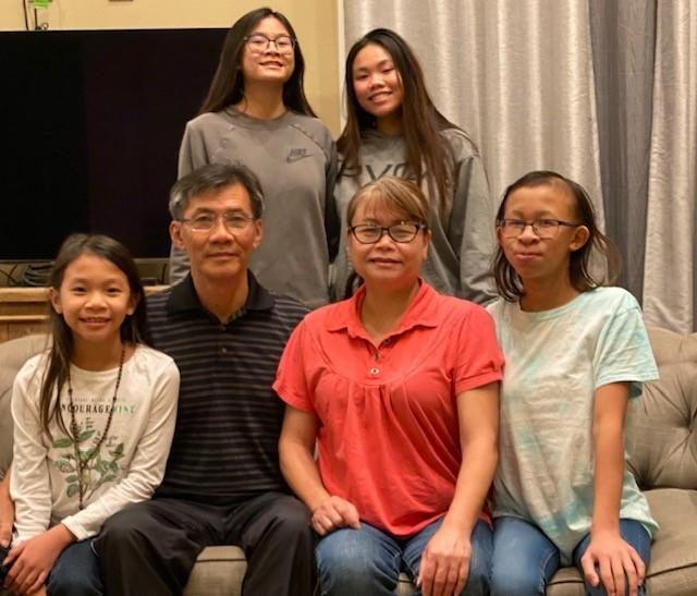 Michael Nguyen sits with his wife and four daughters.