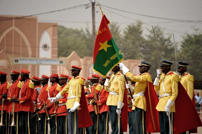 Burkinabe servicemen stand to attention during a ceremony in Nation Square in Ouagadougou on January 25, 2016, in tribute to the victims of the January 15 attack which killed 30 people