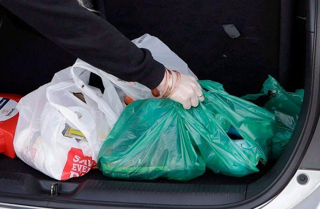 A shopper in New Zealand is seen here putting plastic bags filled with groceries in the trunk of her car. A proposed ban on single-use plastics could make these bags much harder to find in Canada.