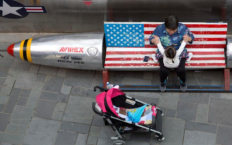 A woman tends to a child near a promotional gimmick in the form of a bomb and the U.S. flag outside a U.S. apparel shop in Beijing - AP
