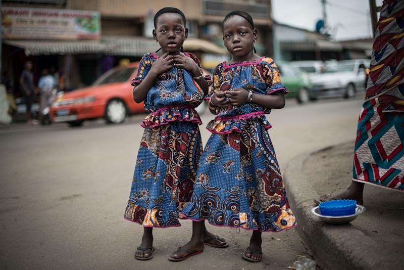 Rasidatou and Latifatou, 4, pose for a portrait on a street in the Koumassi district of Abidjan, Ivory Coast, on July 25, 2017.