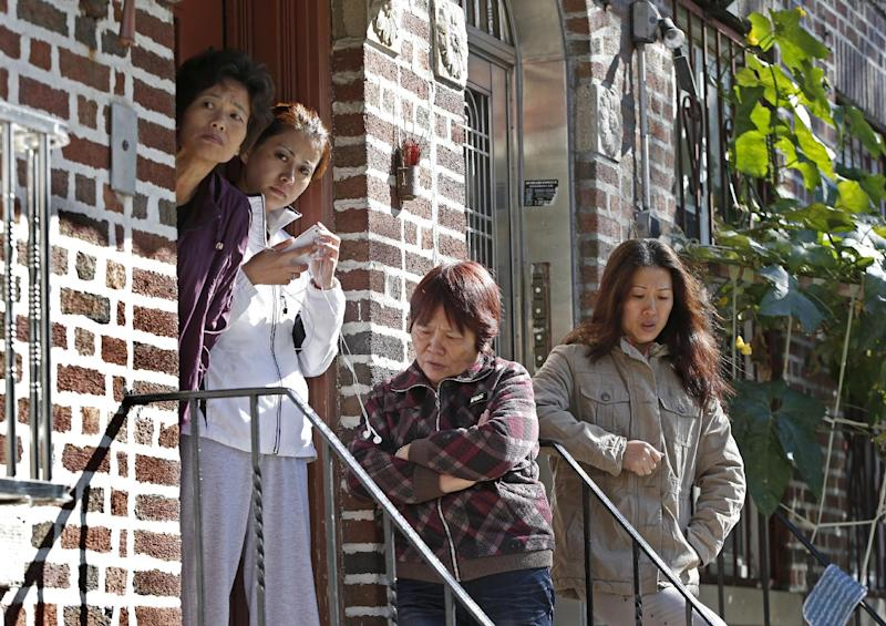 Women gather on the steps of an apartment building opposite the scene of a brutal fatal stabbing, Sunday, Oct. 27, 2013, in New York. Police say a mother and her four young children were killed in a late night stabbing rampage at a Sunset Park, Brooklyn, home. A Chinese immigrant, 25-year-old Ming Don Chen, was arrested Sunday on five counts of murder in the deaths of his cousin's wife and her four children. (AP Photo/Kathy Willens)