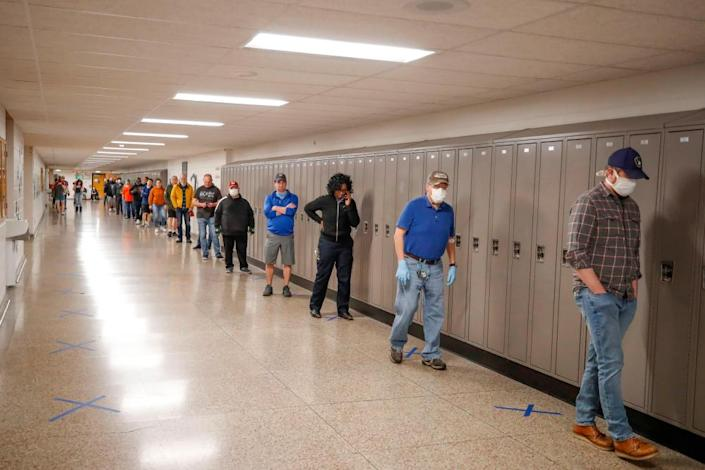 People wait in line to vote in a Democratic presidential primary election outside the Hamilton High School in Milwaukee, Wisconsin, on April 7, 2020.