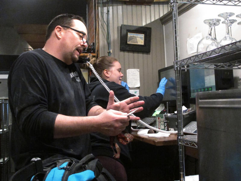 In this March 24, 2020 photo, Michael Morin, left, and Sylvia Pappa, right, take telephone orders at Federico's Pizza in Belmar N.J. The owners of the business took out a $50,000 line of credit to ensure that their employees can stay on the payroll for at least two months during the virus outbreak. That prompted an outpouring of donations from customers wanting to send pizzas to hospital workers and first responders. (AP Photo/Wayne Parry)