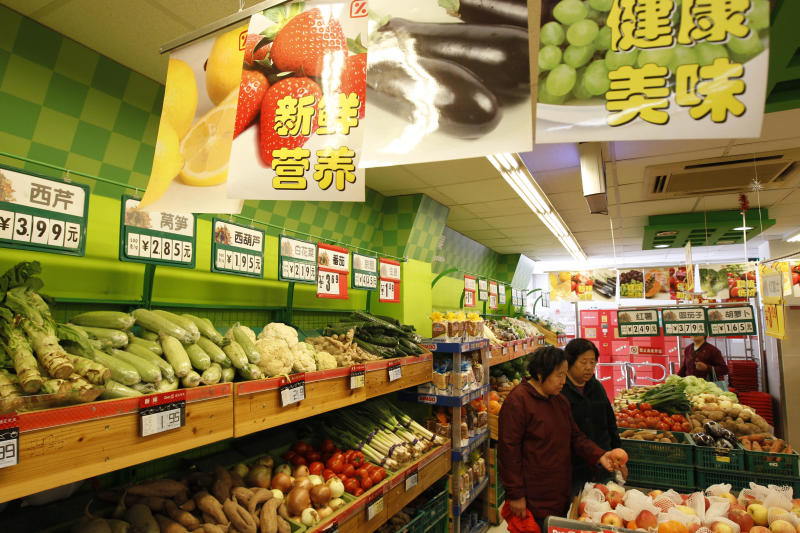 Chinese women shop for fresh fruits at a supermarket in Beijing, China, Thursday, April 12, 2012. The World Bank cut its growth forecast for China on Thursday, adding to warnings the world's second-largest economy might slow too abruptly, and said Beijing should be ready to launch a new stimulus if needed. (AP Photo/ Vincent Thian)