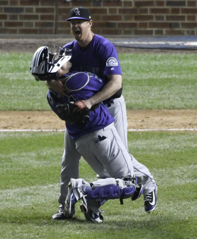 Colorado Rockies catcher Tony Wolters, front, and Colorado Rockies relief pitcher Scott Oberg, rear, celebrate their win in the National League wild-card playoff baseball game, Wednesday, Oct. 3, 2018, in Chicago. The Rockies won 2-1 in thirteen innings. (AP Photo/David Banks)