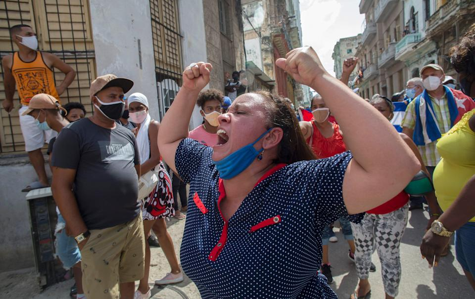 A woman shouts pro-government slogans as anti-government protesters march in Havana, Cuba, Sunday, July 11, 2021. Hundreds of demonstrators took to the streets in several cities in Cuba to protest against ongoing food shortages and high prices of foodstuffs.