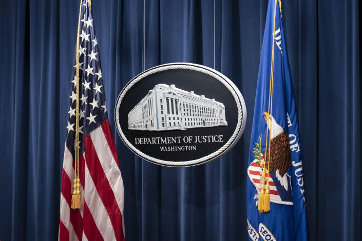 """A sign for the Department of Justice is seen ahead of a news conference Tuesday, Jan. 12, 2021, in Washington. Federal prosecutors are looking at bringing """"significant"""" cases involving possible sedition and conspiracy charges in last week's riot at the U.S. Capitol. (Sarah Silbiger/Pool via AP)"""