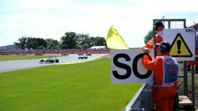 Mercedes' Nico Rosberg drives by waved yellow flags