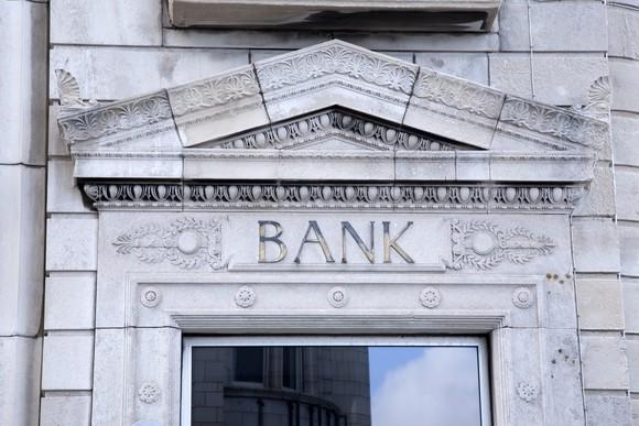 Entrance to a bank building, with bank engraved over the doorway.