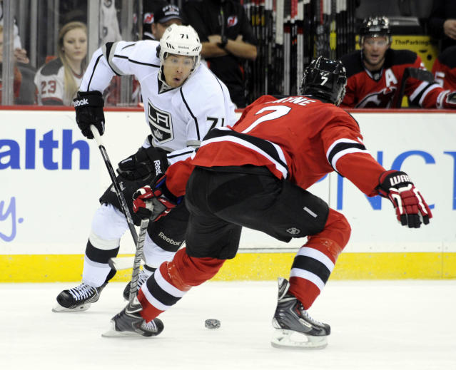 Los Angeles Kings' Jordan Nolan, left, eyes the puck as New Jersey Devils' Mark Fayne defends during the first period of an NHL hockey game Friday, Nov. 15, 2013, in Newark, N.J. (AP Photo/Bill Kostroun)