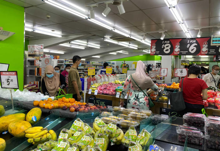 People wear face masks while shopping for groceries at a supermarket in Singapore, Friday, May 14, 2021. Singapore further tightened its COVID-19 measures as it sought to control an increase in untraceable coronavirus infections in the city-state. (AP Photo/Zen Soo)