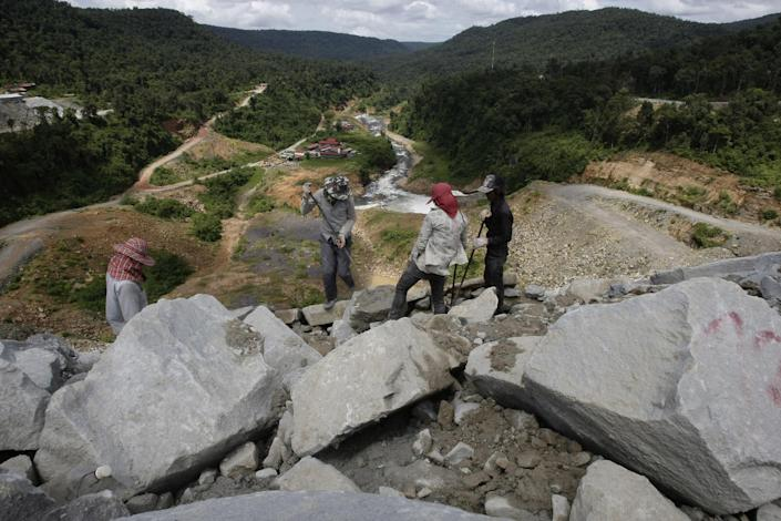 In this Oct. 6, 2012, local workers adjust stones at a dam construction site by China National Heavy Machinery Corporation on the Tatay River in Koh Kong province, some 210 kilometers (130 miles) west of Phnom Penh, Cambodia. Up a sweeping, jungle valley in a remote corner of Cambodia, Chinese engineers and workers are raising a 100-meter- (330-foot) high dam over the protests of villagers and activists. Only Chinese companies are willing to tame the Tatay and other rivers of Koh Kong province, one of Southeast Asia's last great wilderness areas. (AP Photo/Heng Sinith)