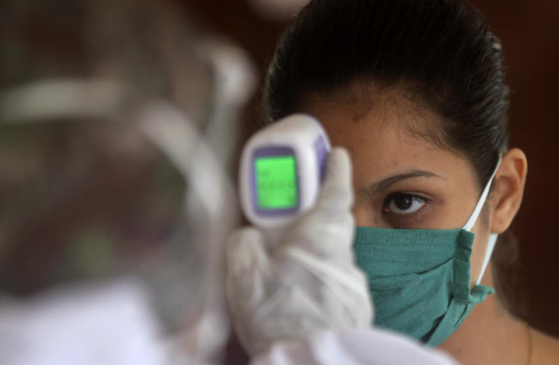 A health worker takes takes the temperature of a girl at a residential building in Mumbai, India, Wednesday, July 22, 2020. With a surge in coronavirus cases in the past few weeks, state governments in India have been ordering focused lockdowns in high-risk areas to slow down the spread of infections. (AP Photo/Rafiq Maqbool)