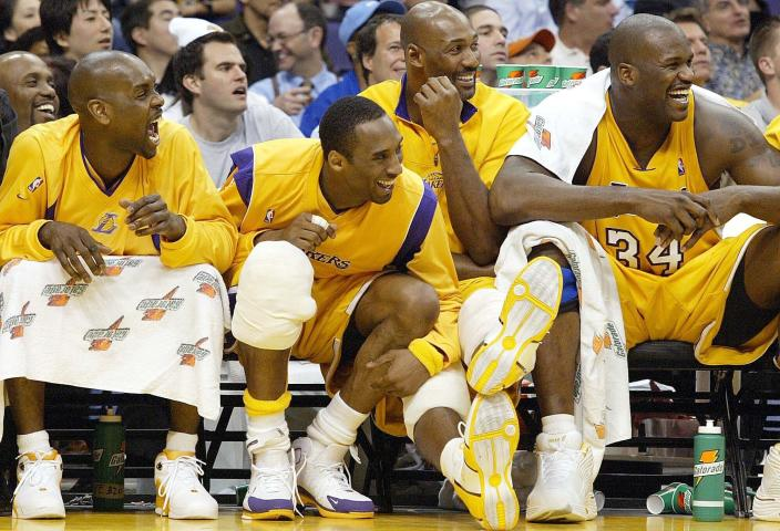 FILE - In this March 30, 2004, from left, Los Angeles Lakers guard Gary Payton, guard Kobe Bryant, forward Karl Malone, and center Shaquille O'Neal smile as they watch their teammates play against the New Orleans Hornets during the fourth quarter at Staples Center in Los Angeles. Kobe Bryant's legacy may be stronger than ever. Tuesday, Jan. 26, 2021, marks the anniversary of the crash that took the lives of Bryant, his daughter Gianna and seven other people. (AP Photo/Nam Y. Huh, File)