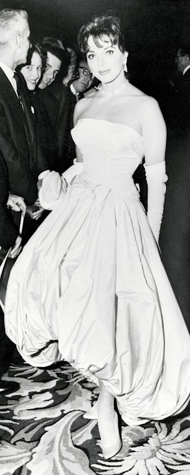<p>Joan Collins clearly turned heads in this bubble hem gown-and in the '50s no formal look was complete without elbow-length gloves. </p>
