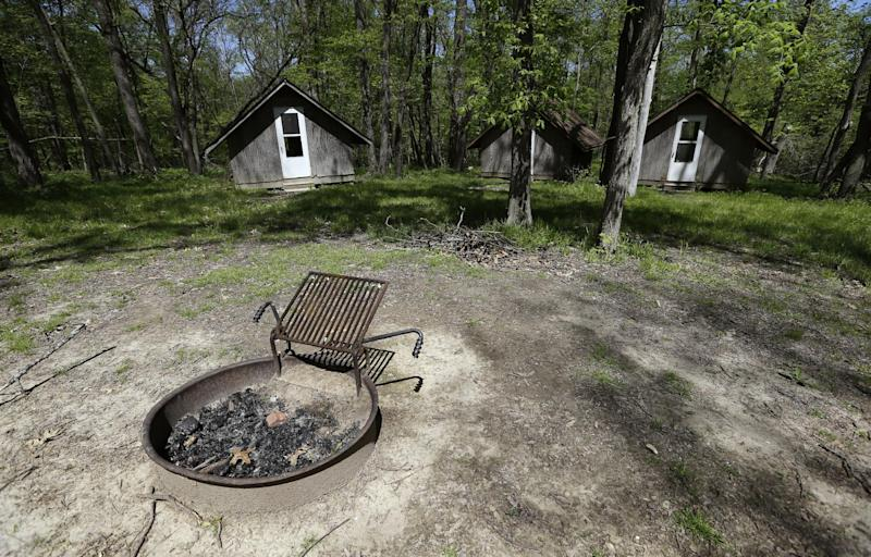 This Tuesday, May 14, 2013, file photo shows a fire pit and cabins at the Camp Conestoga Girls Scouts camp, in New Liberty, Iowa. In 2013, financial stress has prompted many local councils to consider selling off old summer camps, both to gain revenue and reduce maintenance costs. (AP Photo/Charlie Neibergall)