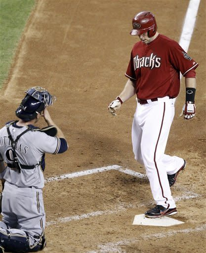 Arizona Diamondbacks' Paul Goldschmidt, right, steps on home plate in front of Milwaukee Brewers catcher George Kontaras, left, after hitting a solo home run off Brewers pitcher Randy Wolf in the fourth inning of a baseball game on Sunday, May 27, 2012, in Phoenix.(AP Photo/Paul Connors)