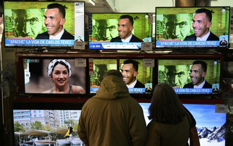 A couple watches LED televisions displayed at a store in Buenos Aires