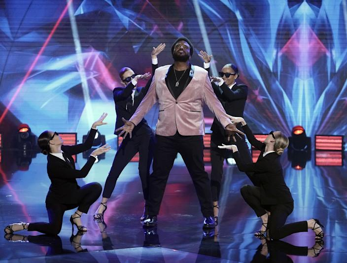 Women dancers in sunglasses and suits surround host Craig Robinson.