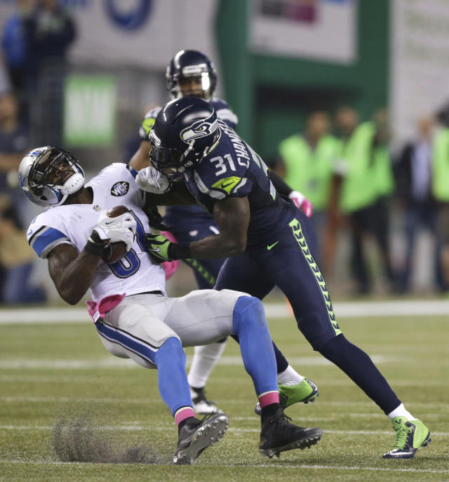 FILE - In this Oct. 5, 2015, file photo, Seattle Seahawks strong safety Kam Chancellor (31) hits Detroit Lions wide receiver Calvin Johnson (81) during the second half of an NFL football game in Seattle. The former Lions superstar said the team wanted him to change his story regarding one of the many concussions he had during his nine-year NFL career. (AP Photo/Scott Eklund, File)