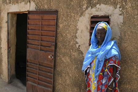 A woman stands outside a house at the site of an attack by gunmen on Fulani herders in Ogossagou