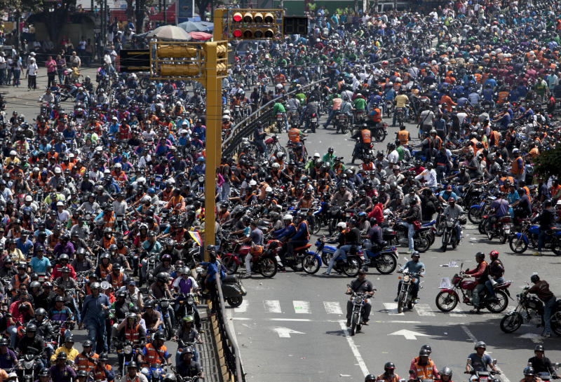 Motorcyclists protest a proposed nighttime curfew for two-wheelers in Caracas, Venezuela, Friday, Jan. 31, 2014. President Nicolas Maduro's government this month lent its support to proposals to ban motorcycles from circulating at night, arguing that the vehicles are used to carry out murders and kidnappings that have proliferated recently. (AP Photo/Alejandro Cegarra)
