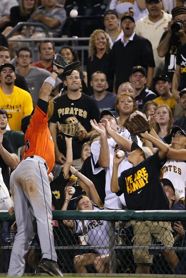 Miami Marlins first baseman Garrett Jones reaches into the stands to make the catch on a foul ball by Pittsburgh Pirates' Starling Marte to end the seventh inning of a baseball game in Pittsburgh on Tuesday, Aug. 5, 2014. (AP Photo/Gene J. Puskar)