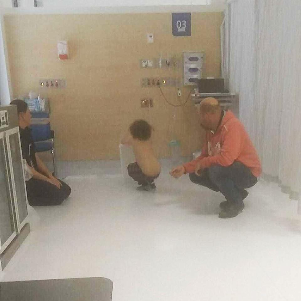 The nurse (left) playing makeshift basketball with Jace (centre) at Dubbo Hospital.