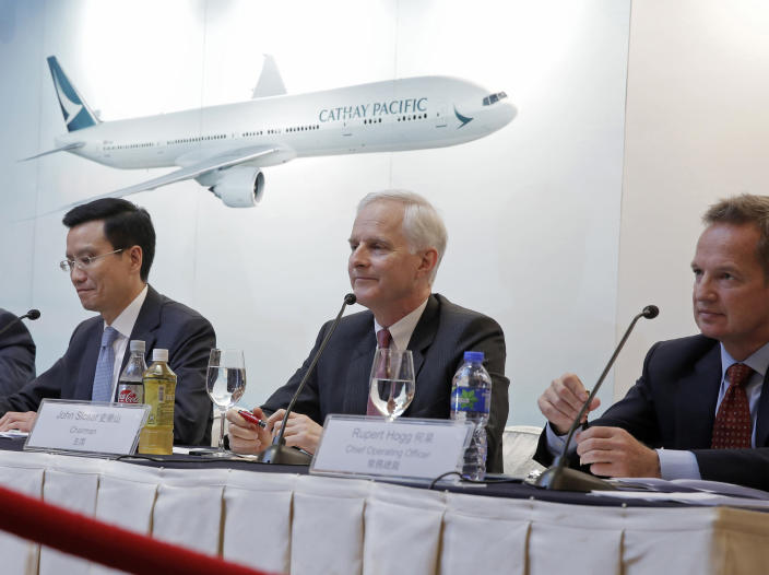 FILE - In this March 15, 2017, file photo, from right, Cathay Pacific Chief Operating Officer Rupert Hogg, Chairman John Slosar and Chief Executive Ivan Chu attend a news conference as they announce the company result in Hong Kong. Hogg resigned Friday, Aug. 16, 2019, following pressure by Beijing on the Hong Kong carrier over participation by some of its employees in anti-government protests. (AP Photo/Kin Cheung, File)