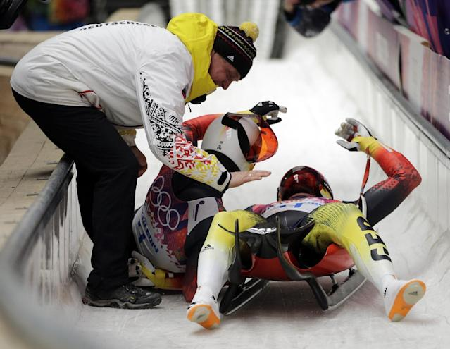 The doubles team of Tobias Wendl and Tobias Arlt from Germany celebrate in the finish area after their final run to win the gold medal during the men's doubles luge at the 2014 Winter Olympics, Wednesday, Feb. 12, 2014, in Krasnaya Polyana, Russia.(AP Photo/Jae C. Hong)