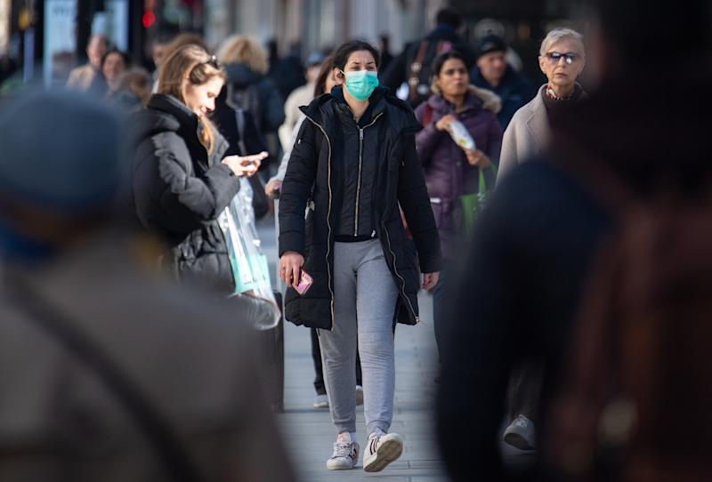 A woman wearing protective face masks on Oxford Street, central London. On Thursday evening, an older patient, reported to be a woman in her 70s, became the first person in the UK to die after being diagnosed.