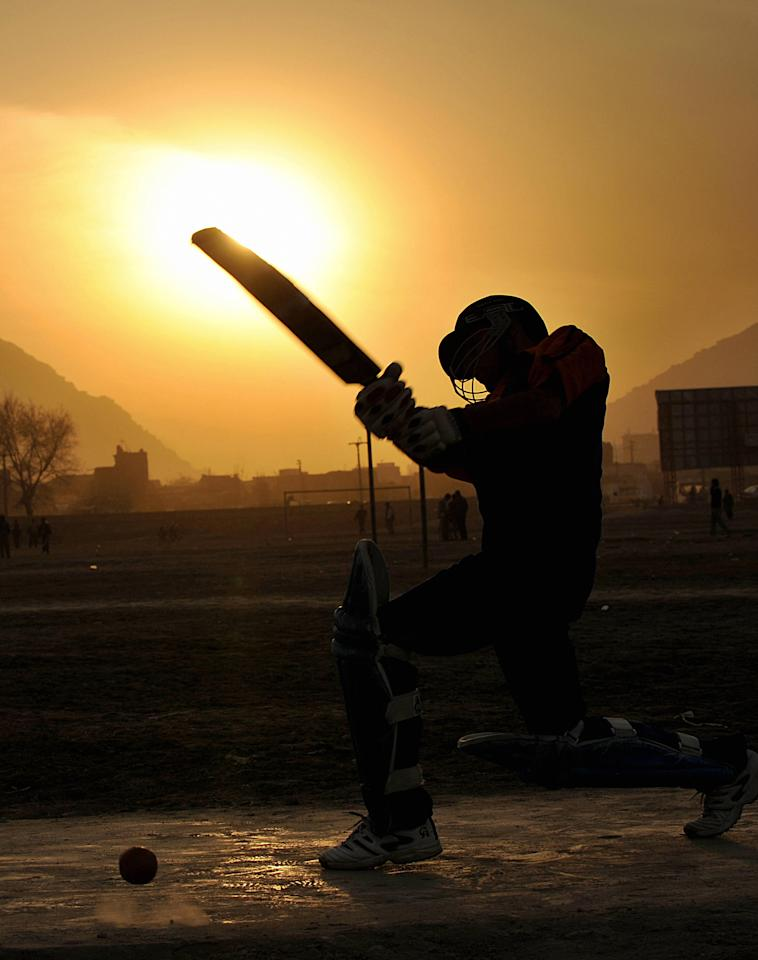 An Afghan boy plays cricket on the grounds in front of the stadium in Kabul on February 27, 2008. Cricket is popular among Afghans who have lived in Pakistan and recently returned to their country after decades of war.   AFP PHOTO/SHAH Marai (Photo credit should read SHAH MARAI/AFP/Getty Images)