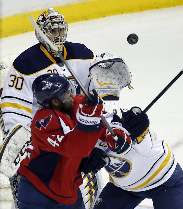 Buffalo Sabres goalie Ryan Miller (30) prepares to catch a shot over Washington Capitals right wing Joel Ward (42) and left wing Matt Moulson (26) in the third period of an NHL hockey game, Sunday, Jan. 12, 2014, in Washington. The Sabres won 2-1 in a shootout. (AP Photo/Alex Brandon)