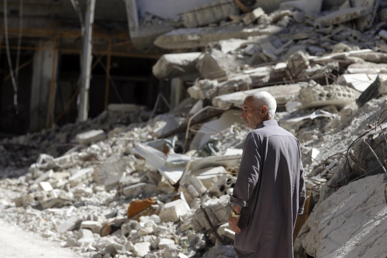 A man walks by damage and debris in Ain Tarma, in the eastern Ghouta suburb of Damascus August 21, 2014. A year has passed since the chemical attacks on Ghouta. REUTERS/Bassam Khabieh (SYRIA - Tags: POLITICS CIVIL UNREST CONFLICT)