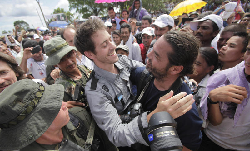 French journalist Romeo Langlois, center left, embraces fellow journalist Carlos Villalon, from Chile, in San Isidro in southern Colombia, Wednesday, May 30, 2012. Langlois, who was taken by rebels of the Revolutionary Armed Forces of Colombia (FARC) on April 28 when they attacked troops he was accompanying on a cocaine-lab eradication mission, was handed over by the rebels to a delegation that included a French diplomat. (AP Photo/Fernando Vergara)