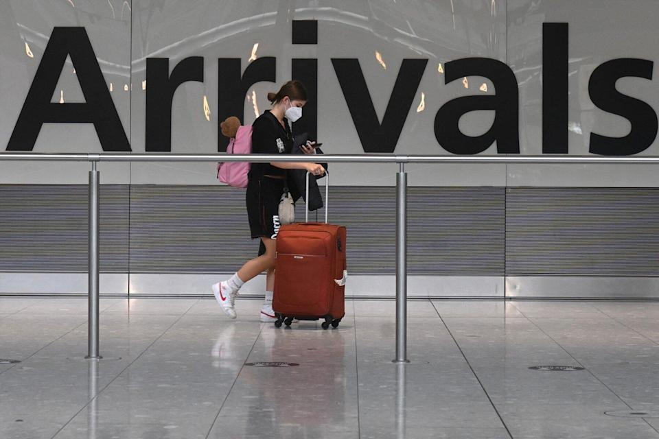 pasenger pulls roller suitcase at Heathrow airport