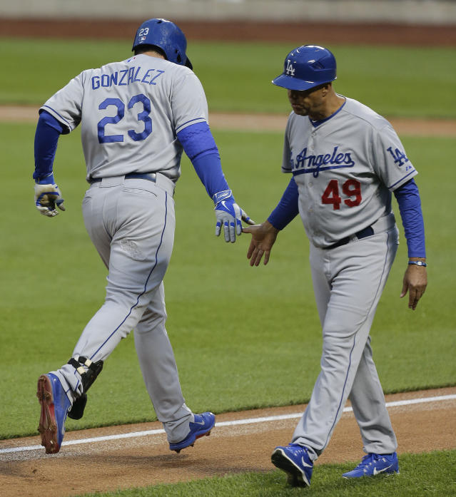 Los Angeles Dodgers' Adrian Gonzalez (23) is greeted by third base coach Lorenzo Bundy as he rounds the bases after hitting solo home run against the New York Mets during the second inning of a baseball game, Wednesday, May 21, 2014, in New York. (AP Photo/Julie Jacobson)