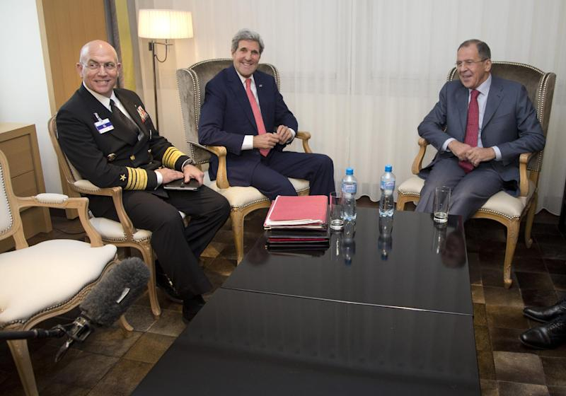 From left, Vice Admiral Kurt Tidd, U.S. Secretary of State John Kerry and Russia's Foreign Minister Sergei Lavrov look to a boom microphone held by a member of the media, lower left corner, as they sit together during a photo opportunity during a meeting, Saturday, Nov. 23, 2013, in Geneva, Switzerland, during the Iran nuclear talks. U.S. Secretary of State John Kerry and foreign ministers of other major powers joined Iran nuclear talks on Saturday, throwing their weight behind a diplomatic push to complete a deal after envoys reported progress on key issues blocking an interim agreement to curb the Iranian program in return for limited sanctions relief. (AP Photo/Carolyn Kaster, Pool)