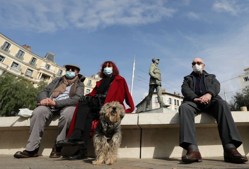 People wearing protective face masks sit in a local market in Nice