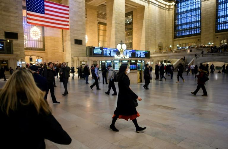 A woman walks through New York's Grand Central Station wearing a mask -- the state is one of at least 15 in the United States where cases of new coronavirus have been found