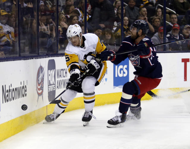 Pittsburgh Penguins defenseman Zach Trotman, left, passes the puck against Columbus Blue Jackets forward Brandon Dubinsky during the second period of an NHL hockey game in Columbus, Ohio, Saturday, March 9, 2019. (AP Photo/Paul Vernon)