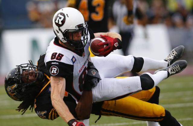 Ottawa Redblacks' Matt Carter catches a pass against the Hamilton Tiger-Cats' Courtney Stephen (L) during the first half of their CFL football in Hamilton, July 26, 2014. REUTERS/Mark Blinch (CANADA - Tags: SPORT FOOTBALL)