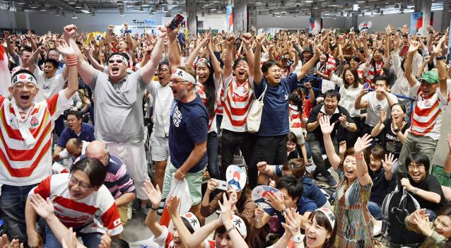 Japan team's fans celebrate the team's win over Scotland at the Rugby World Cup Pool A game as they watch the game in a public viewing in Tokyo, Sunday, Oct. 13, 2019. (Kyodo News via AP)