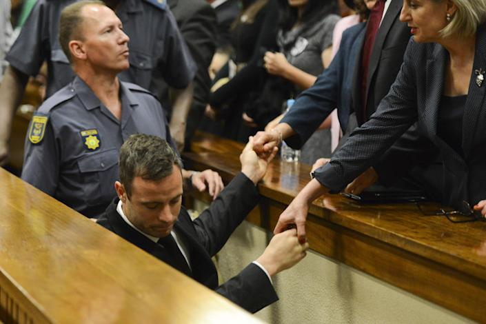 Oscar Pistorius holds the hands of family members as he is taken down to the holding cells after being sentenced to five years imprisonment at the High Court in Pretoria, on October 21, 2014 (AFP Photo/Herman Verwey)