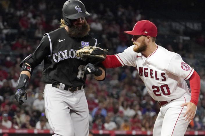Colorado Rockies' Charlie Blackmon, left, is tagged out by Los Angeles Angels first baseman Jared Walsh as he runs to first during the fifth inning of a baseball game Monday, July 26, 2021, in Anaheim, Calif. (AP Photo/Mark J. Terrill)