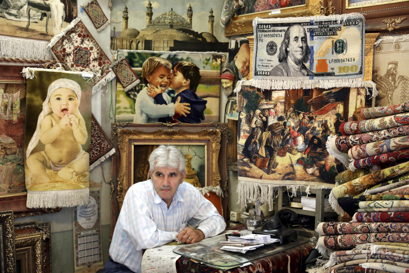"""A carpet merchant sits at his shop in the old main bazaar in Tehran, Iran, Tuesday, July 2, 2019.  From an English-language teacher hoping for peace to an appliance salesman who applauded Donald Trump as a """"successful businessman,"""" all said they suffered from the economic hardships sparked by re-imposed and newly created American sanctions. (AP Photo/Ebrahim Noroozi)"""