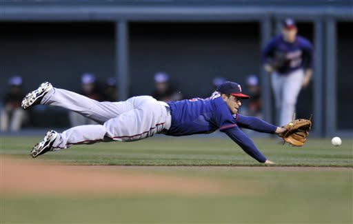Minnesota Twins second baseman Brian Dozier dives for a ground ball hit by Baltimore Orioles Manny Machado in the first inning of a baseball game on Saturday, April 6, 2013, in Baltimore. Machado earned a single on the play. (AP Photo/Gail Burton)