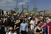 People march across the Szabadsag, or Freedom Bridge over the River Danube in downtown Budapest during a gay pride parade in Budapest, Hungary, Saturday, July 24, 2021. Rising anger over policies of Hungary's right-wing government filled the streets of the country's capital on Saturday as thousands of LGBT activists and supporters marched in the city's Pride parade. (AP Photo/Anna Szilagyi)