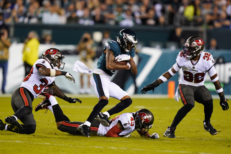 Philadelphia Eagles wide receiver DeVonta Smith (6) runs with the ball past Tampa Bay Buccaneers Ross Cockrell, bottom, Mike Edwards, right, and Jordan Whitehead during the second half of an NFL football game Thursday, Oct. 14, 2021, in Philadelphia. (AP Photo/Matt Rourke)